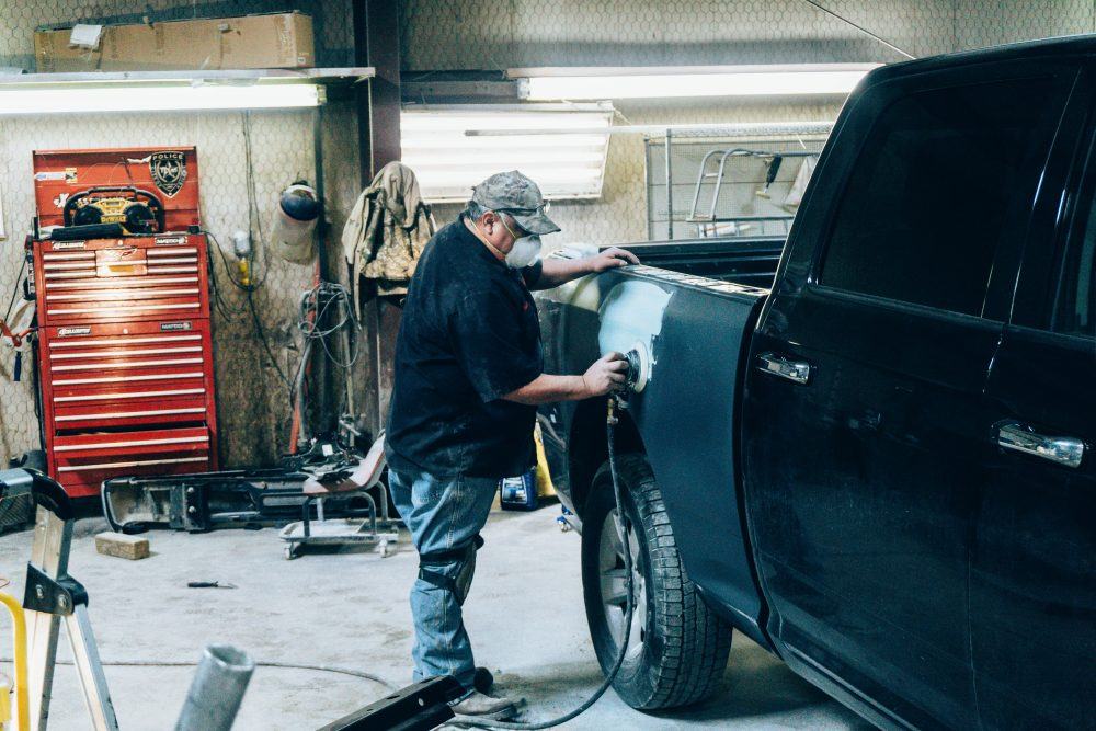 Gibbs Paint and Body- Employee Sanding A Truck
